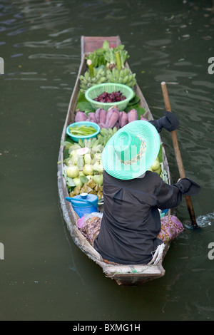 Thai woman paddling through the canals in a long boat full of vegetables - Stock Photo