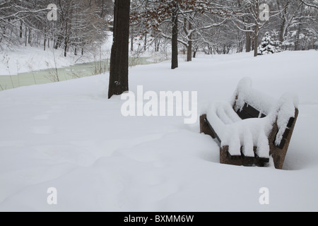 A snow covered park bench in Minneapolis, Minnesota - Stock Photo