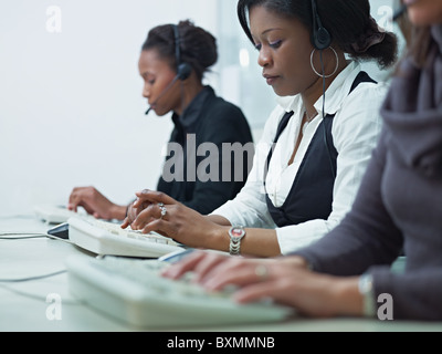 multiethnic group of female customer service representatives talking on the phone and typing on computer keyboard. - Stock Photo