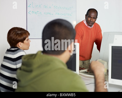 Computer class with hispanic student asking question to male indian teacher. Horizontal shape, focus on background - Stock Photo
