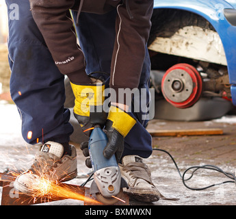 A teenage male using an angle grinder whilst working on repairing the chassis of a car, wearing protective gloves. - Stock Photo