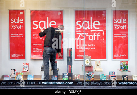 A SHOPKEEPER FROM WHATERSTONE IS HANGING A SALE SIGN IN HIS SHOP WINDOW ON BOXING DAY, LONDON, ENGLAND, BRITAIN - Stock Photo