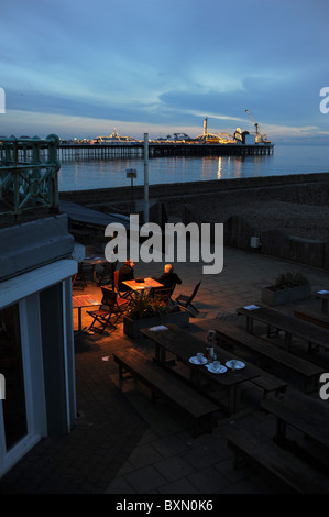 Couple sitting at seafront cafe bar at dusk by the Palace Pier in Brighton at dusk - Stock Photo