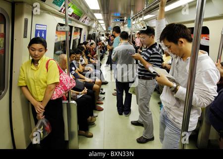Singapore: Passengers in a car of MRT (Mass Rapid Transport) subway train system - Stock Photo