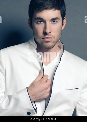 Fashion photo of a young smiling man wearing a white blazer - Stock Photo