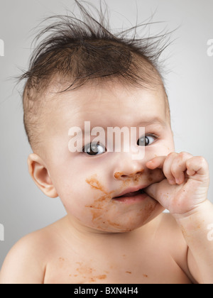 Artistic portrait of a seven month old baby boy with messy hair and smudged with food face sucking his thumb - Stock Photo