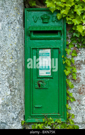 Green postbox with initials VR, Victoria Regina, from reign of Queen Victoria, at Fethard-on-Sea, Co. Wexford, Ireland - Stock Photo