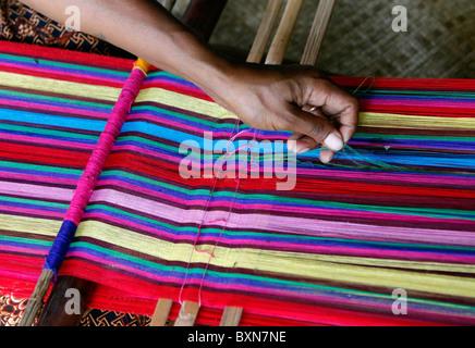 Woman traditionally weaving tais on backstrap loom in Timor Leste (East Timor) - Stock Photo