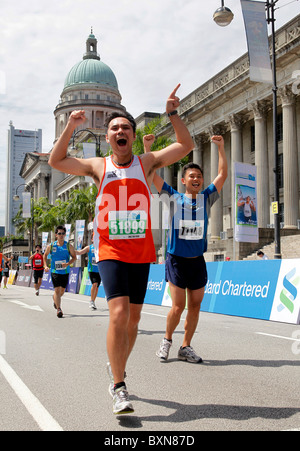 Runners at the Singapore Marathon 2010, Supreme Court and City Hall in the background. - Stock Photo