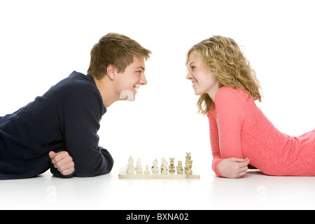 Attractive teenagers lying down playing chess, isolated on white background - Stock Photo