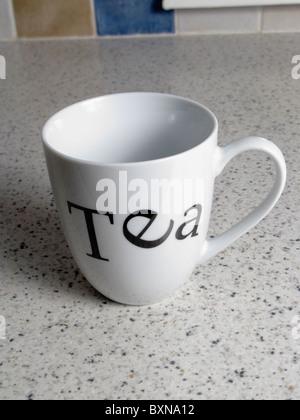empty white China mug with Tea written on it on kitchen worktop typeface font with serif - Stock Photo
