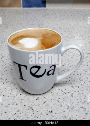 cup of coffee Drink of coffee with frothed milk in a China mug with Tea written on it on kitchen worktop. Confused - Stock Photo