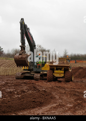 excavator digger and dumptruck on road building site uk in winter - Stock Photo