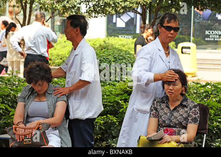 Blind Masseuses massage patients on streets of Kunming, China - Stock Photo