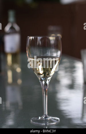 Summer time glass of white wine outdoors on the patio. - Stock Photo