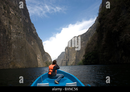 A tourist takes pictures from a boat in the Sumidero Canyon in Tuxla Gutierrez, Chiapas, Mexico, February 18, 2010. - Stock Photo