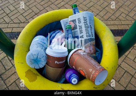 Railway station platform waste bin full with recyclable waste, paper cups, plastic bottles and newspaper. - Stock Photo