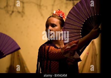 A Flamenco dancer, or bailaora, performs using a hand fan in the Tablao Flamenco El Cardenal in Cordoba, Andalusia, - Stock Photo