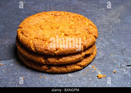 Three ginger biscuits stacked and placed on a piece of slate - Stock Photo