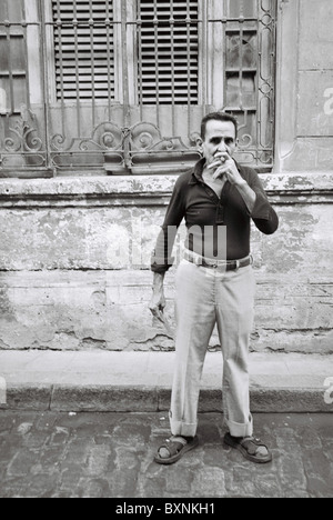 Man smoking a cigar in the street. - Stock Photo