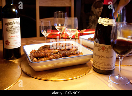 Sausages wrapped in bacon and bottles of red wine on the christmas dinner table, UK - Stock Photo
