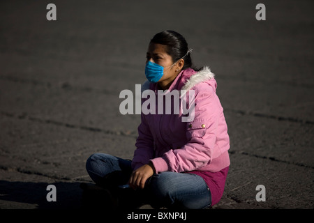 A young woman wearing a mask as a precaution against swine flu sits in Mexico City's main Zocalo square, May 1, - Stock Photo