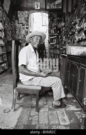 Man sitting fixing old music player in book store. - Stock Photo