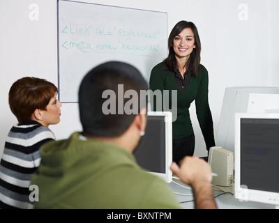 Computer class with caucasian female teacher talking to hispanic student. Horizontal shape, focus on background - Stock Photo