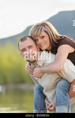 young attractive couple piggy-back ride at a mountain lake - Stock Photo