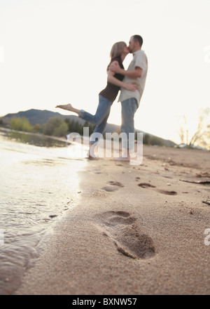 modern couple kissing each other on beach with footprints in sand - Stock Photo