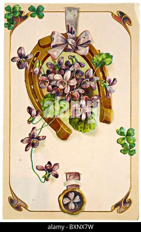 Vintage postcard of violets, shamrocks and a horseshoe - Stock Photo