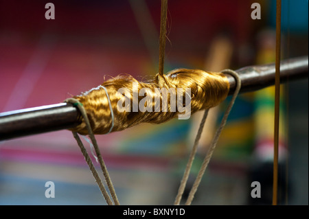 Gold silk thread on a spindle, part of a hand loom for making silk sari's in India - Stock Photo