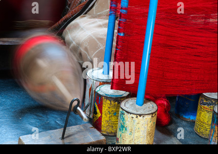 Indian woman working a sari handloom with coloured silk thread on spindles. Andhra Pradesh, India - Stock Photo