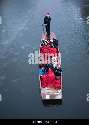 Winter punting in the snow and ice on the river Cam, Cambridge - Stock Photo