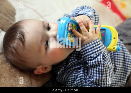 6 month old little boy laying in his children room, on a blanket, smiling, looking happy and friendly. Playing with - Stock Photo