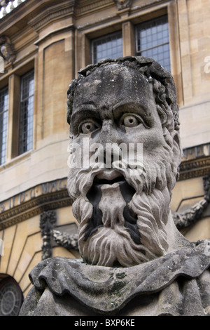An old stone bust stares from the Sheldonian Theatre in Oxford England - Stock Photo