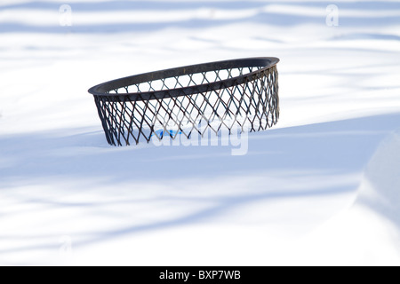 A trash can buried almost up to its rim in New York CIty's Riverside Park on the day after a blizzard hit the city - Stock Photo