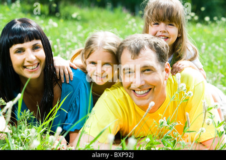 Portrait of happy family lying on the grass and looking at camera - Stock Photo