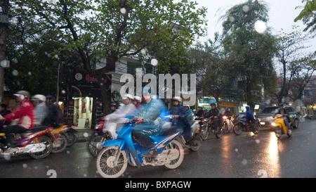 Motorscooters on a busy Hanoi street in the rain - Stock Photo