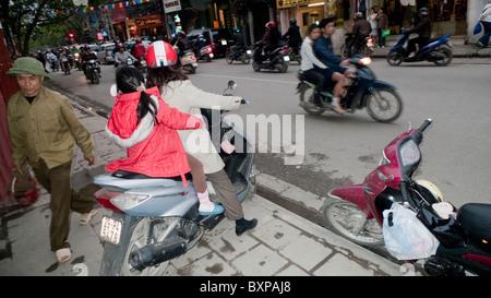 Motorscooters on a busy Hanoi street - Stock Photo