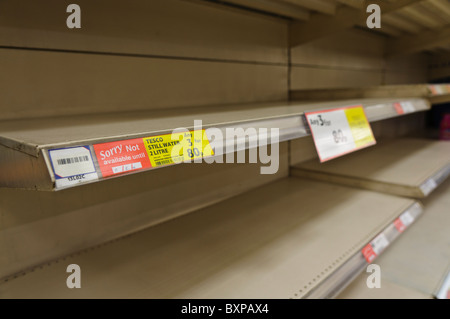 Panic buying of bottled water in shops during water shortage leaves shelves empty. - Stock Photo