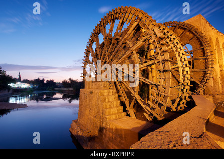 Traditional Syrian waterwheels ('Norias') at dusk on the Orontes river in Hama, Syria.  In front of the 'Four Norias - Stock Photo