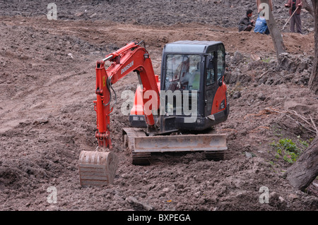 A heavy plant construction digger in a mud in a building site in Yangzhou China - Stock Photo