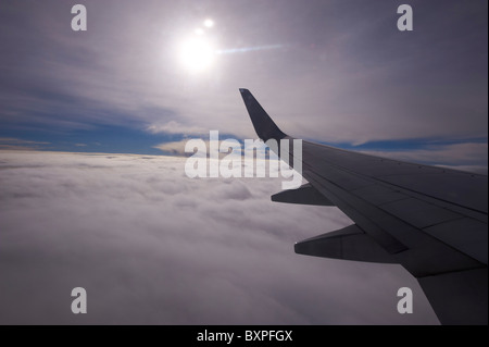 Looking out over clouds through airliner window - Stock Photo