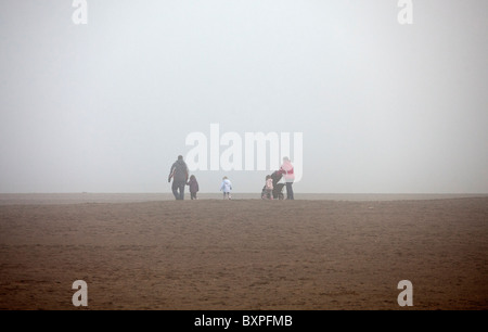 Skegness, Lincolnshire, UK.Skegness, Lincolnshire, UK. A family brave the fog on the beach in Skegness. - Stock Photo