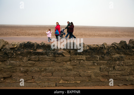 Skegness, Lincolnshire, UK.Skegness, Lincolnshire, UK. A family walk along the sea front promenade in misty weather. - Stock Photo