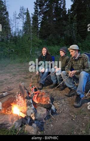 young family camping and roasting hot dogs over a fire - Stock Photo