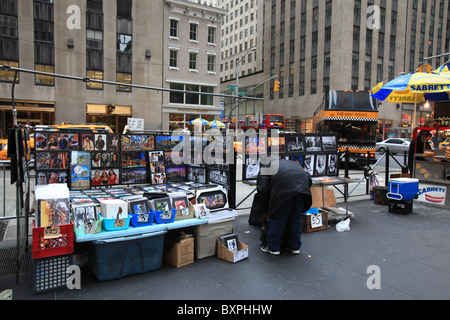 A taxi-tours bus cruises by a tradesman selling tourist photographs on Sixth Avenue of New York city in Christmas - Stock Photo