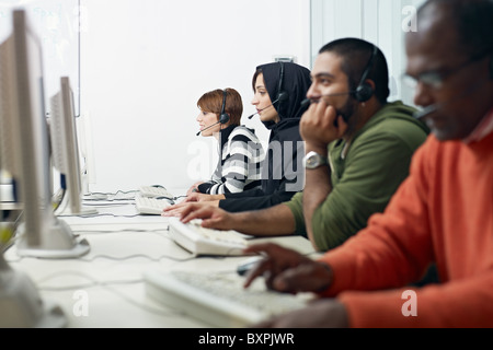 Multiethnic computer class with indian, middle eastern, hispanic and caucasian people training with pc. - Stock Photo