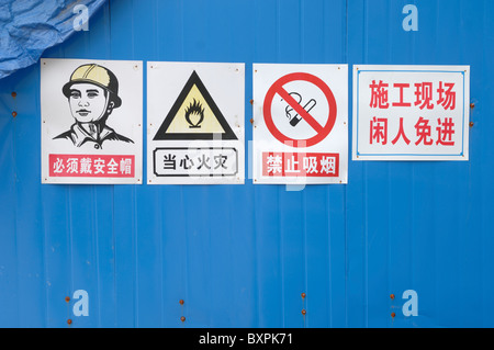 Health and Safety signs on a hoarding outside a construction site in Yangzhou China - Stock Photo